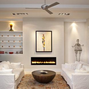 Exempel på ett modernt vardagsrum, med beige väggar och en bred öppen spis