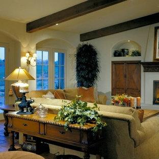 Foto di un ampio soggiorno stile americano aperto con pareti bianche, pavimento in terracotta, camino classico e cornice del camino in intonaco