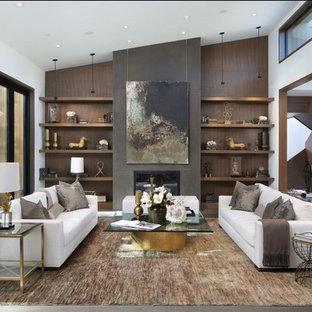 Ejemplo de salón abierto, actual, grande, con paredes marrones, suelo de madera oscura, chimenea tradicional, suelo marrón y marco de chimenea de yeso