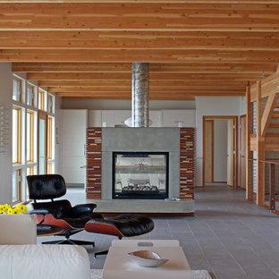 Immagine di un soggiorno minimal aperto e di medie dimensioni con sala formale, pareti bianche, pavimento con piastrelle in ceramica, camino bifacciale e cornice del camino in cemento