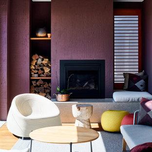 Inredning av ett modernt stort allrum med öppen planlösning, med lila väggar, mellanmörkt trägolv, en standard öppen spis, en spiselkrans i metall och beiget golv