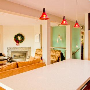 Ispirazione per un soggiorno design di medie dimensioni e aperto con pareti verdi, pavimento in legno massello medio, camino classico, cornice del camino piastrellata e TV a parete