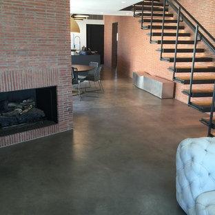 Inspiration för stora industriella loftrum, med ett finrum, röda väggar, betonggolv, en standard öppen spis, en spiselkrans i tegelsten och grått golv