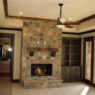 シャーロットの中くらいのトラディショナルスタイルのおしゃれな独立型リビング (ベージュの壁、カーペット敷き、標準型暖炉、石材の暖炉まわり、テレビなし) の写真