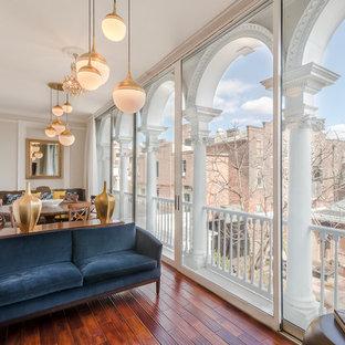 Modelo de salón abierto, tradicional renovado, con paredes beige y suelo de madera en tonos medios