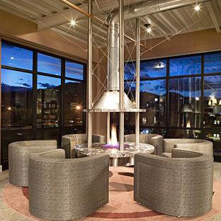 Esempio di un ampio soggiorno industriale aperto con cornice del camino in metallo, pareti beige, camino sospeso, pavimento in travertino, TV a parete, sala formale e pavimento beige