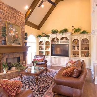 アトランタの大きいトラディショナルスタイルのおしゃれなLDK (フォーマル、黄色い壁、濃色無垢フローリング、吊り下げ式暖炉、石材の暖炉まわり、テレビなし、茶色い床) の写真