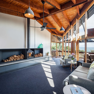 Contemporary open concept living room in Melbourne with a wood stove, a metal fireplace surround, no tv, white walls and carpet.
