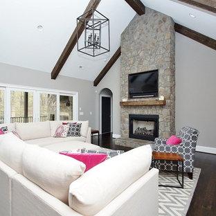 Idee per un grande soggiorno american style aperto con pareti grigie, parquet scuro, camino classico, cornice del camino in pietra e TV a parete