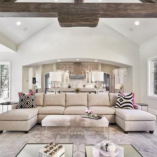 Réalisation d'un très grand salon tradition ouvert avec un mur gris, une cheminée standard et un sol en bois brun.