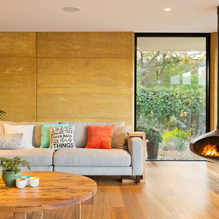 This is an example of a contemporary formal open concept living room in Melbourne with a hanging fireplace.