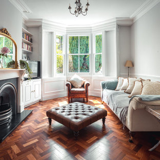Inspiration for a traditional enclosed living room in London with grey walls, dark hardwood flooring, a standard fireplace, a freestanding tv and brown floors.