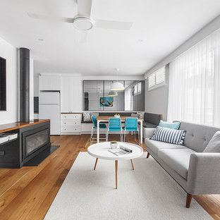 Design ideas for a contemporary living room in Melbourne with white walls, medium hardwood floors, a wall-mounted tv and brown floor.