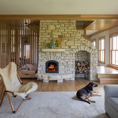 Example of a cottage medium tone wood floor living room design in Minneapolis with white walls and a standard fireplace