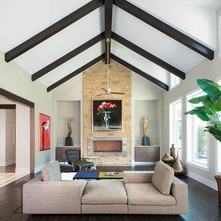 Modelo de salón con barra de bar abierto, contemporáneo, extra grande, con paredes beige, suelo de madera oscura, chimenea lineal y marco de chimenea de piedra