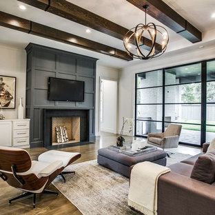 Transitional medium tone wood floor and brown floor living room photo in Dallas with white walls, a standard fireplace and a wall-mounted tv
