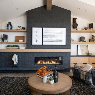 Fernseherloses, Offenes Maritimes Wohnzimmer mit weißer Wandfarbe, hellem Holzboden, Kamin, Kaminumrandung aus Backstein, freigelegten Dachbalken und Ziegelwänden in Orange County