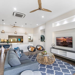 Photo of a large modern open plan living room in Townsville with white walls, vinyl flooring, a wall mounted tv and brown floors.