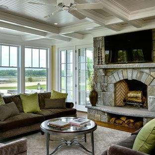 ボストンの中サイズのビーチスタイルのおしゃれなLDK (フォーマル、黄色い壁、無垢フローリング、標準型暖炉、石材の暖炉まわり、壁掛け型テレビ) の写真