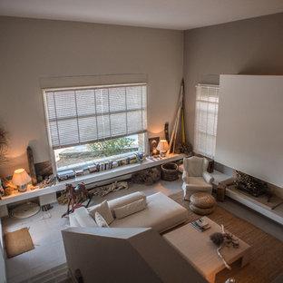 Ispirazione per un soggiorno mediterraneo con pareti grigie, pavimento con piastrelle in ceramica, camino sospeso, cornice del camino in intonaco e TV autoportante