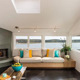 ボストンのビーチスタイルのおしゃれなLDK (白い壁、コンクリートの床、コーナー設置型暖炉、コンクリートの暖炉まわり) の写真