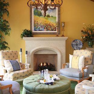 Modelo de salón para visitas cerrado, campestre, pequeño, sin televisor, con paredes amarillas, moqueta, chimenea tradicional, marco de chimenea de piedra y suelo verde