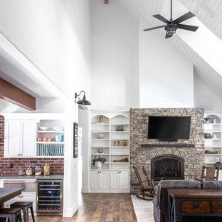 Exempel på ett mycket stort lantligt allrum med öppen planlösning, med vita väggar, vinylgolv, en öppen vedspis, en väggmonterad TV och brunt golv