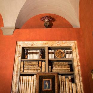 Idee per un grande soggiorno mediterraneo chiuso con pareti gialle, parquet scuro, camino classico, cornice del camino in pietra e libreria