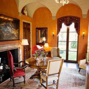 Imagen de biblioteca en casa cerrada, mediterránea, grande, con parades naranjas, suelo de madera oscura, chimenea tradicional y marco de chimenea de piedra