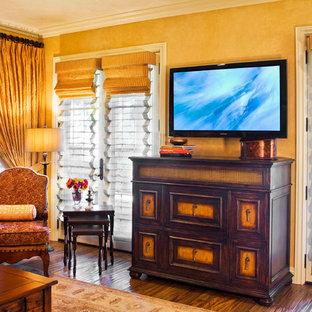 Modelo de salón para visitas cerrado, mediterráneo, sin chimenea, con parades naranjas, suelo de madera oscura, televisor colgado en la pared y suelo marrón