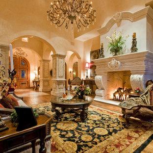 フェニックスの巨大な地中海スタイルのおしゃれな独立型リビング (フォーマル、ベージュの壁、濃色無垢フローリング、標準型暖炉、石材の暖炉まわり、テレビなし、茶色い床) の写真