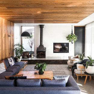 Modelo de salón abierto, contemporáneo, grande, con paredes blancas, suelo de cemento, estufa de leña, suelo gris, marco de chimenea de hormigón y televisor retractable