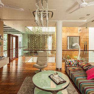 Ejemplo de salón abierto, actual, con paredes marrones, suelo de madera en tonos medios y televisor colgado en la pared
