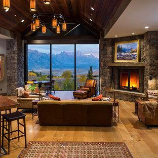 Immagine di un grande soggiorno stile rurale aperto con pavimento in legno massello medio, camino classico, cornice del camino in pietra, pareti beige, nessuna TV e pavimento marrone