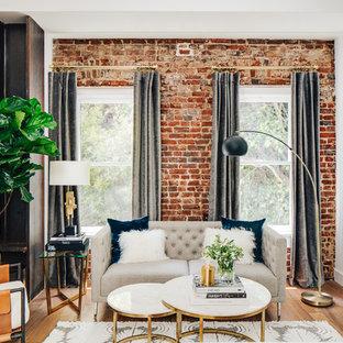 Immagine di un piccolo soggiorno minimalista stile loft con pareti bianche, pavimento in legno massello medio e camino classico