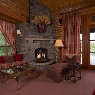 Large rustic formal enclosed living room in Jackson with brown walls, carpet, a corner fireplace, a stone fireplace surround, no tv and red floors.