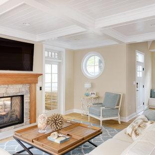 他の地域のビーチスタイルのおしゃれなLDK (ベージュの壁、淡色無垢フローリング、両方向型暖炉、石材の暖炉まわり、壁掛け型テレビ) の写真