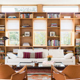 Example of a mid-sized trendy open concept medium tone wood floor and brown floor living room library design in Los Angeles with white walls, a standard fireplace and a brick fireplace