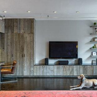 Foto på ett mellanstort industriellt loftrum, med ett finrum, grå väggar, mörkt trägolv, en väggmonterad TV och brunt golv
