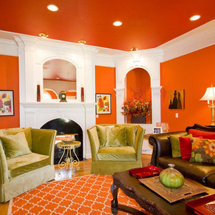 他の地域のトラディショナルスタイルのおしゃれなリビング (オレンジの壁、無垢フローリング、標準型暖炉) の写真