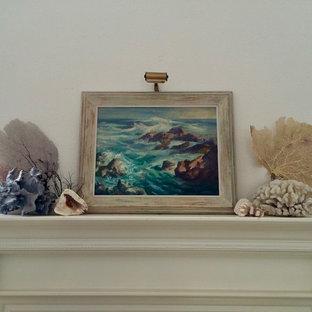 サンディエゴの中サイズのビーチスタイルのおしゃれなリビングロフト (ライブラリー、白い壁、淡色無垢フローリング、標準型暖炉、木材の暖炉まわり、テレビなし、ベージュの床) の写真