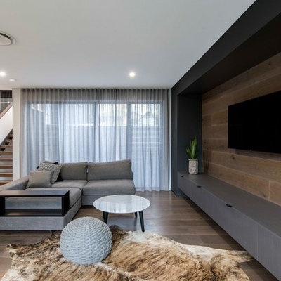 Living room - contemporary open concept medium tone wood floor and brown floor living room idea in Brisbane with white walls and a wall-mounted tv