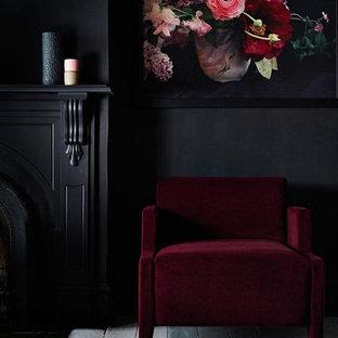 Diseño de salón abierto, tradicional renovado, de tamaño medio, con paredes negras, suelo de contrachapado, chimenea tradicional, marco de chimenea de yeso y suelo gris
