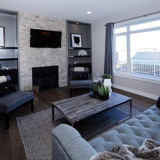 Idee per un soggiorno chic di medie dimensioni e aperto con pareti grigie, parquet scuro, camino classico, cornice del camino in pietra, TV a parete e pavimento marrone