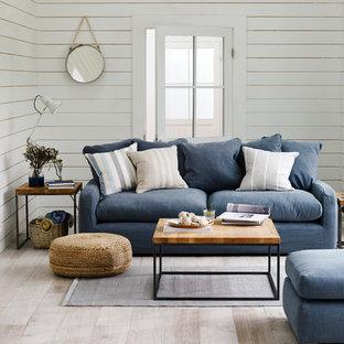 Bild på ett maritimt vardagsrum, med vita väggar, ljust trägolv och beiget golv