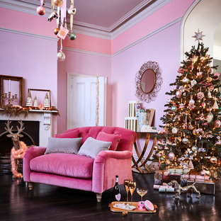 Inspiration for a traditional living room in London with pink walls, dark hardwood floors and a standard fireplace.