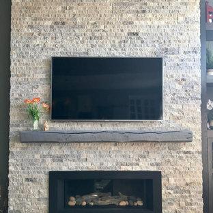 他の地域の中くらいのラスティックスタイルのおしゃれなLDK (マルチカラーの壁、吊り下げ式暖炉、石材の暖炉まわり、壁掛け型テレビ、淡色無垢フローリング、グレーの床) の写真