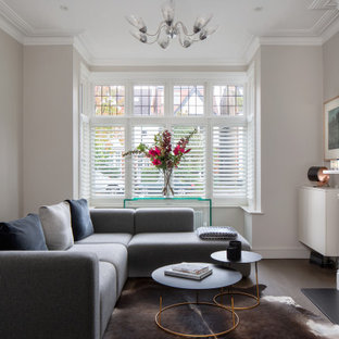 This is an example of a medium sized classic living room in London with grey walls, a wood burning stove and brown floors.