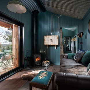 コーンウォールの小さいラスティックスタイルのおしゃれなLDK (青い壁、濃色無垢フローリング、コーナー設置型暖炉、金属の暖炉まわり、内蔵型テレビ、茶色い床) の写真