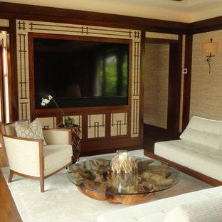 マイアミの中くらいのトロピカルスタイルのおしゃれなリビング (ベージュの壁、無垢フローリング、暖炉なし、壁掛け型テレビ、茶色い床) の写真